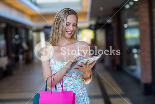 Smiling woman with shopping bags using tablet computer
