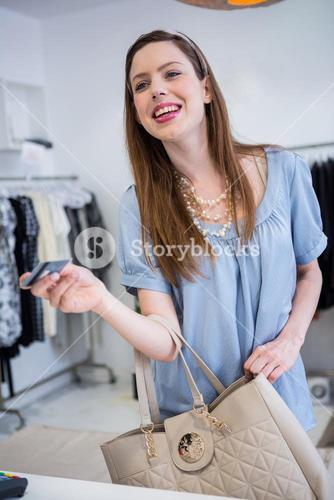 Brunette paying at till with credit card
