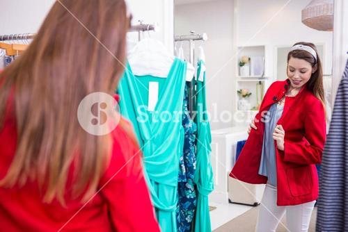 Brunette trying on a red coat