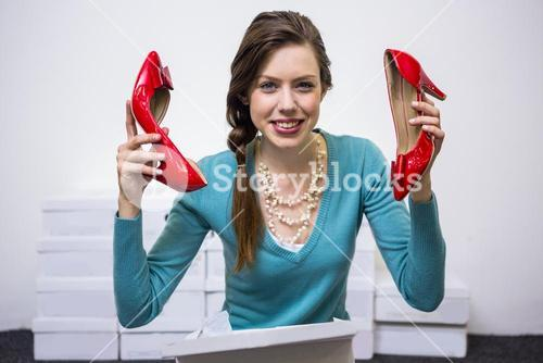 Happy brunette holding up red shoes