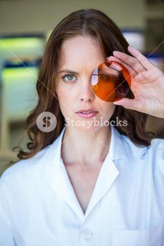 Serious optician holding up lens