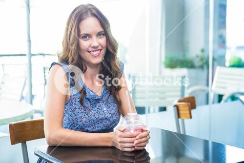 Pretty brunette having a smoothie