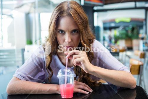 Pretty brunette sipping on a smoothie