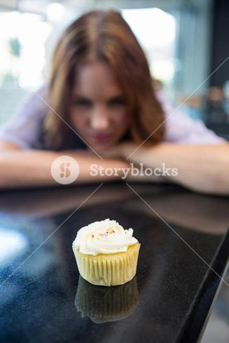 Pretty brunette looking at cupcake