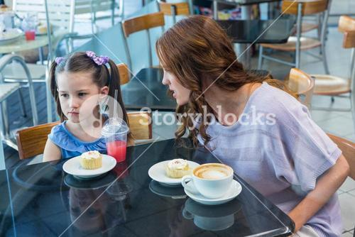 Mother and daughter arguing at table