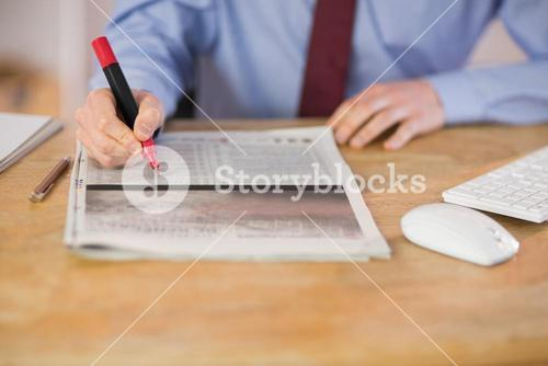 Businessman marking the newspaper with marker