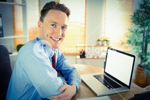 Happy businessman working with laptop