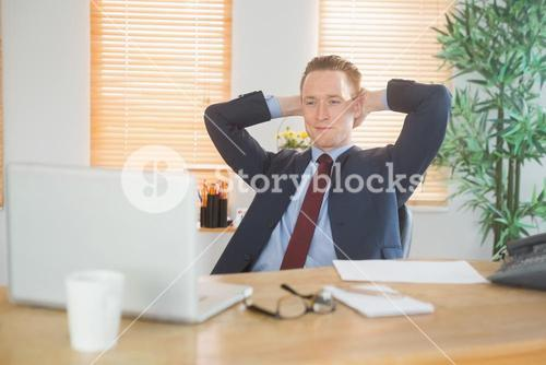 Relaxed businessman sitting back at desk