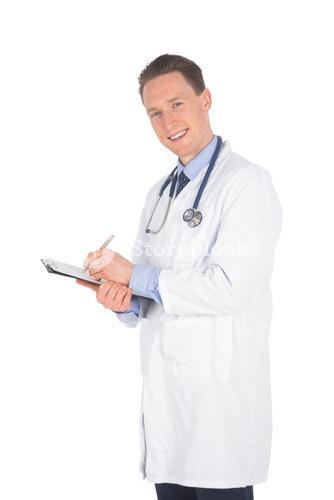 Smiling doctor writing on a clipboard