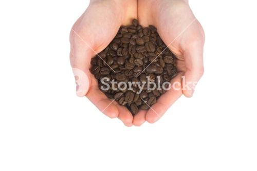 Close up view of hands showing coffee beans