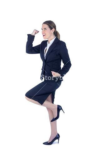 Pretty businesswoman doing a running victory pose