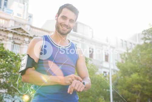 Smiling handsome athlete setting heart rate watch