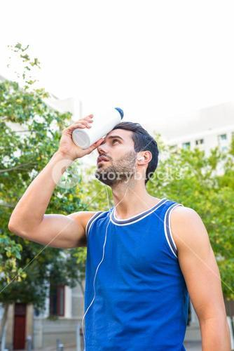 Handsome athlete cooling his forehead with bottle