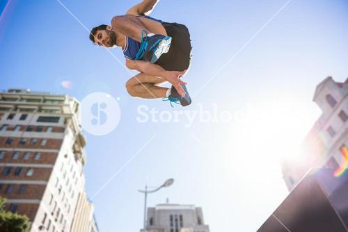 Handsome athlete jumping off the column
