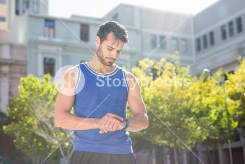 Focused handsome athlete setting heart rate watch