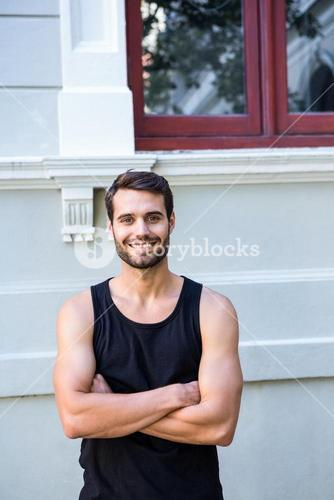 Smiling handsome athlete in front of a building