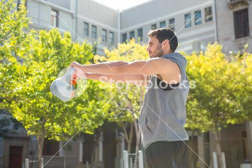 Handsome athlete lifting kettle bell