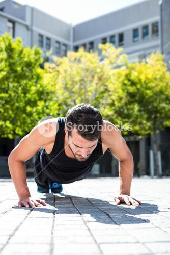 Handsome athlete doing push-ups on the floor