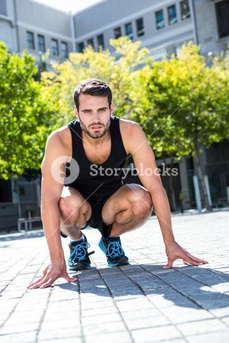 Handsome athlete in a squatting stance
