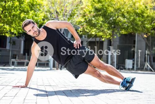 Handsome athlete doing a side plank