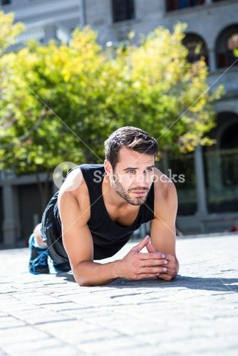 Handsome athlete doing a plank exercise