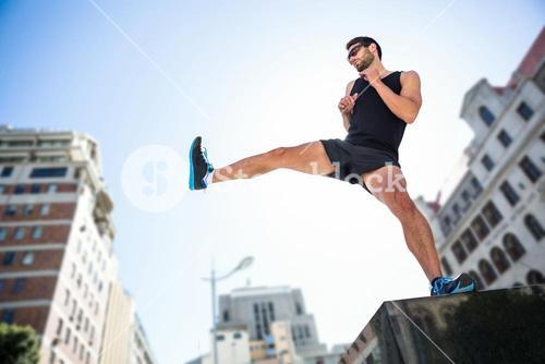 Handsome athlete kicking in the air