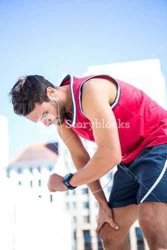 Exhausted athlete looking at his stopwatch