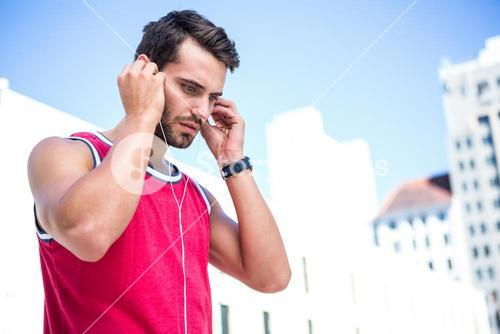 Serious handsome athlete putting on his earphones
