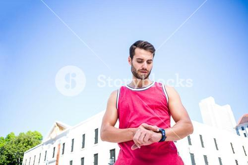 Handsome athlete adjusting his stopwatch