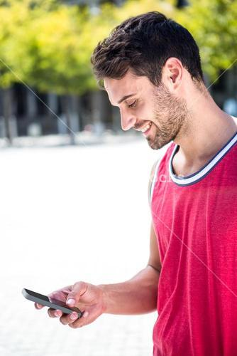Smiling handsome athlete sending a text
