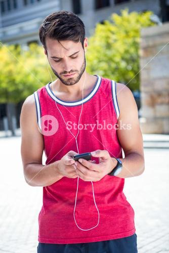 Handsome athlete sending a text