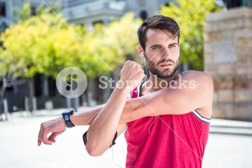 Handsome athlete doing arms stretching