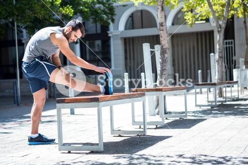 Handsome athlete doing leg stretching on a bench