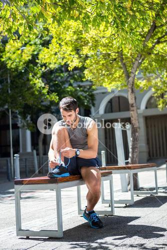 Handsome athlete tying shoelaces on a bench