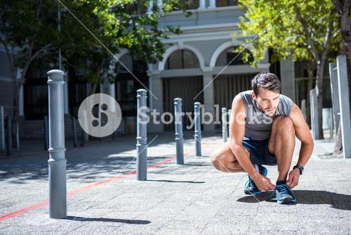 Handsome athlete tying his shoe laces