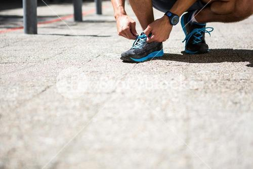 Athletic man tying his shoe laces