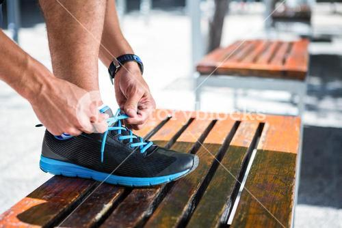 Athletic man tying his shoelaces on the bench