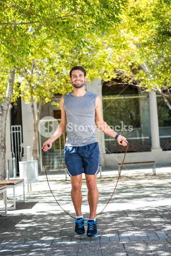 Handsome athlete doing jumping rope