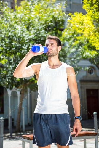 Handsome athlete drinking out of bottle