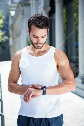 Concentrated handsome athlete setting heart rate watch