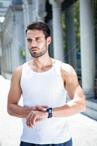 Concentrated handsome athlete checking heart rate watch
