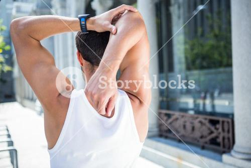 Rear view of athlete stretching his arm