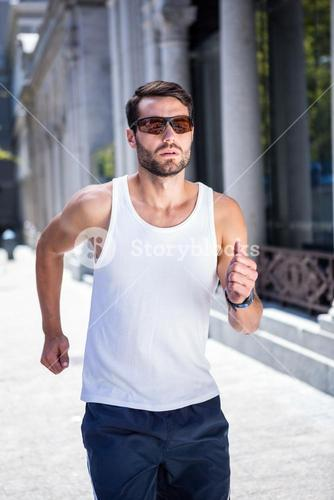 Handsome athlete with sunglasses jogging