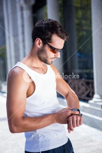 Handsome athlete with sunglasses setting heart rate watch