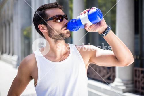 Handsome athlete with sunglasses drinking out of bottle