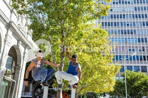 Happy friends doing parkour in the city