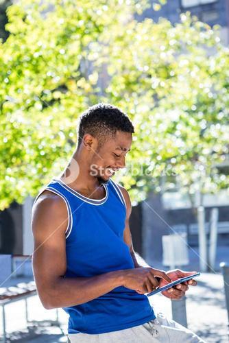 Smiling athletic man using tablet computer