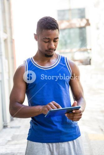 Athletic man using tablet computer