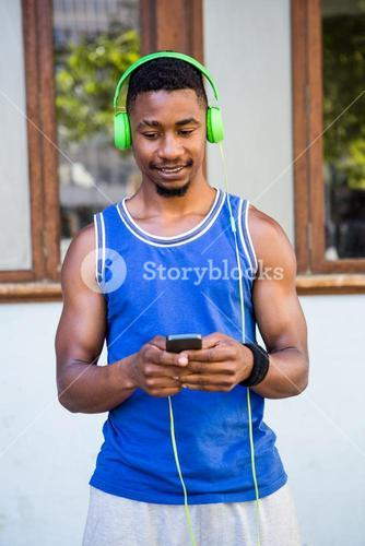 An handsome athlete listening to music