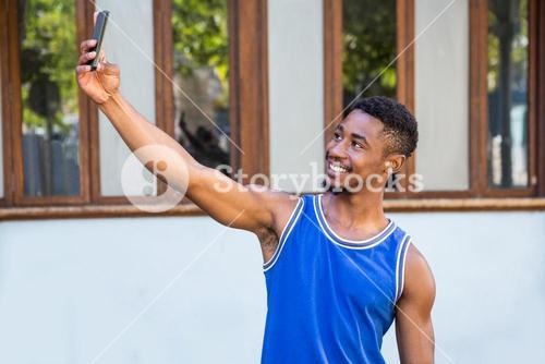 An happy handsome athlete taking a selfie